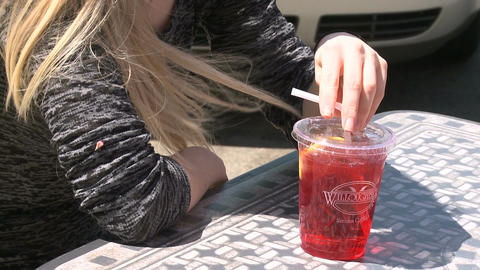 A girl at a sidewalk cafe with a drink with a straw (1 of 2) Live Action