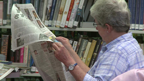 Mature woman reading a newspaper in the library (1 of 2) Footage