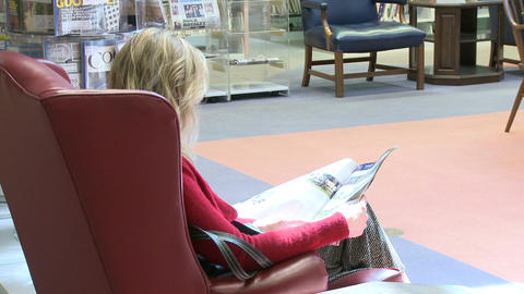 Young woman reading a magazine in the library Live Action