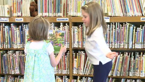 A little girl looking a t her friends book ビデオ