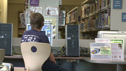 Young boy using a computer at the library Footage