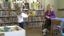 A child getting books for her mother to read to her (1 of 3) Live Action