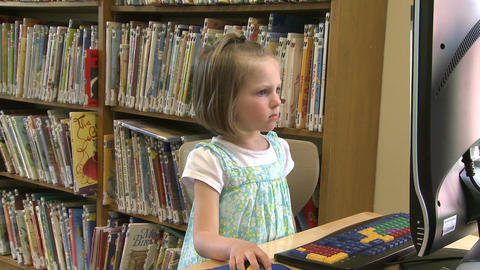 Small child looking at the computer screen in the library Footage