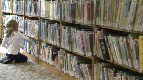 Little girl looking through rows of children's books (4 of 4) Footage