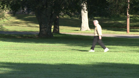Older man walking through park for exercise Footage