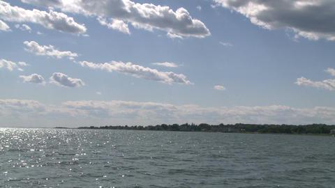 Ocean water glistening below puffy clouds Footage