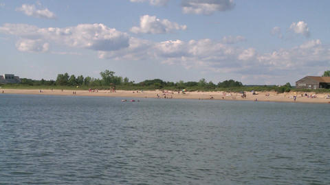 Puffy white clouds over a sandy shoreline (2 of 6) Live Action