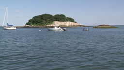 A small tree lined island with boats moored in front (1 of 3) Footage