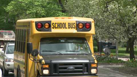 Small school bus traveling on road (3 of 5) Live Action