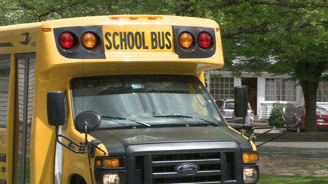 Small school bus traveling on road (4 of 5) Live Action