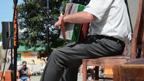 man on chair plays nice cheerful tune with foot hitting throb Footage
