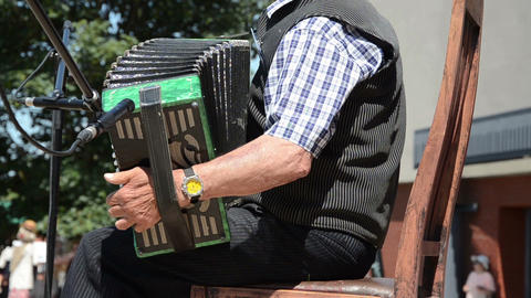 wrinkled senior man playing with old accordion country stage Footage