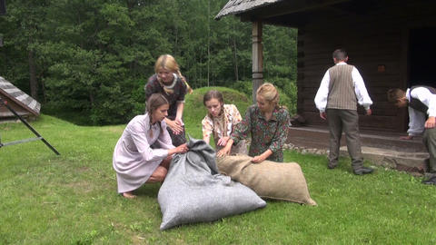 girls with nice dresses cram hay in large linen bags Footage