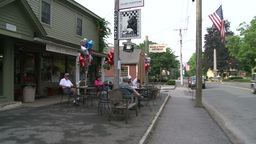 People sitting at tables along the road at a sidewalk cafe Footage