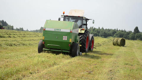 cut grass compress equipment rides through the field work Footage