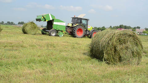 closeup of hay bale and tractor baler discharge round fresh roll Footage