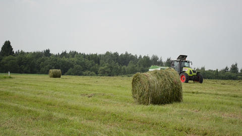 agriculture tractor machine make straw hay bale in autumn field Footage