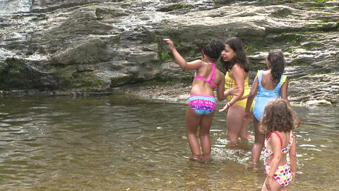 Children wading in the water at the bottom of a waterfall Footage