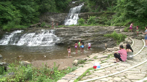 People sitting on a ledge overlooking a waterfall with a pool at the bottom Footage