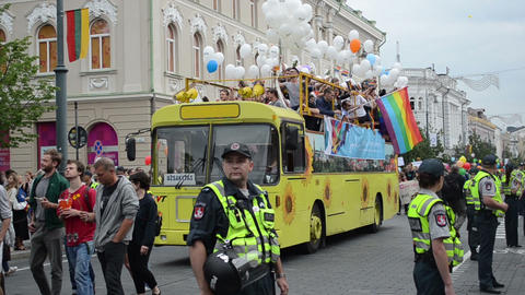 bus drive street town gay parade members white balloons flags Footage