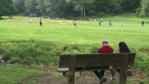 Two people sitting on a bench in a Nature Reserve watching boys play ball Live Action