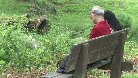 Two people sitting on a bench in a Nature Reserve (1 of 3) Live Action