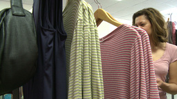 Woman shopper looking at garment along with price tag (3 of 3) Live Action