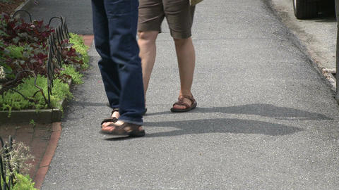 Two people with sandals on stopping in front of a store Footage