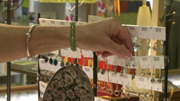 Woman looking at earrings at a jewelry sale Live Action