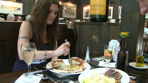 Heavily tattooed man eating a sandwich with a woman eating pizza at restaurant Footage