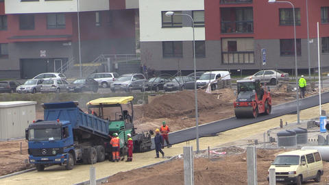 Workers paving asphalt between modern flat houses district Footage
