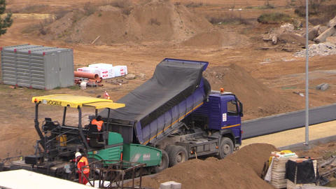 Workers with heavy machines paving asphalt in construction site Footage