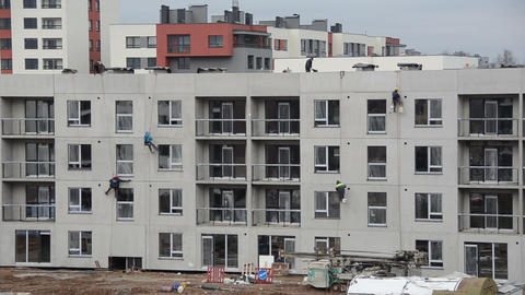 Risky construction site works. High wall insulation hang on rope Footage