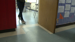 One student going in classroom, and one student coming out Footage