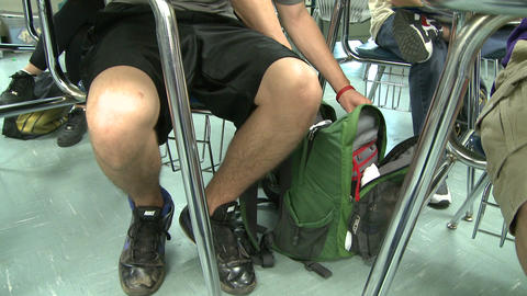 Middle school student reaching in book bag during class Footage