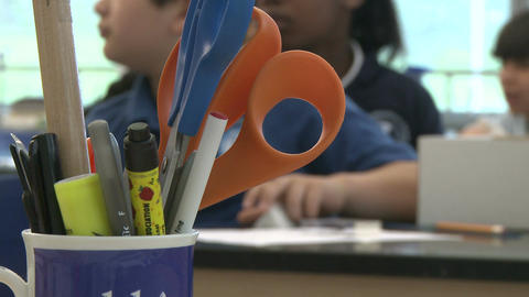A cup with pens, a ruler and scissors with students in back ground (1 of 2) Live Action