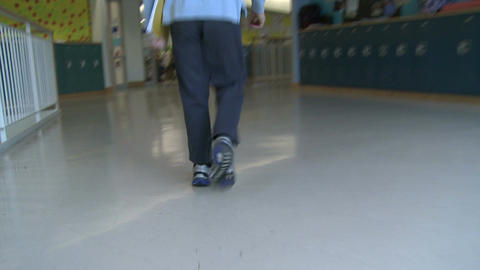 Grammar school boy walks fast through empty hallway Footage