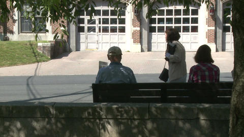 Two people sitting on a bench across from an old fire station Live Action