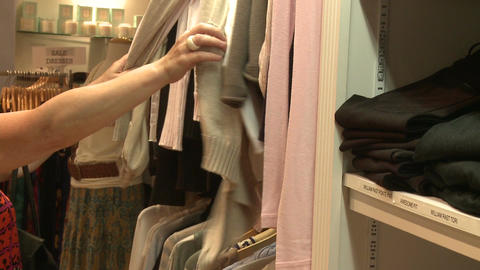 Shopper looking through clothes on a clothes rack Live Action