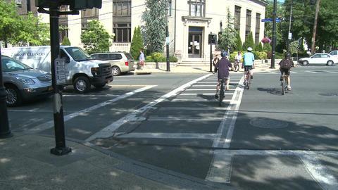 Children with helmets riding bikes across crosswalk Footage