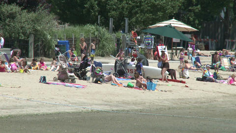 People at small beach with beach umbrellas Footage
