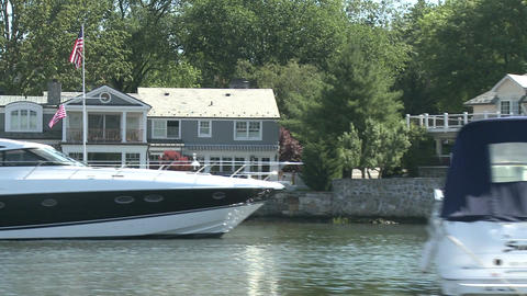 Homes on the water, with boats moored in front Footage