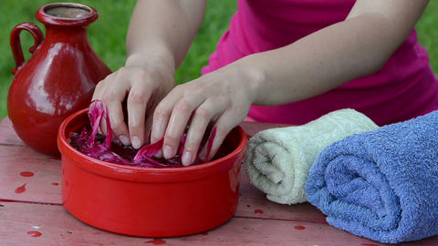 girl dip the hands in a red clay bowl full of peony petals spa Live Action