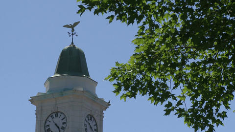 Clock tower with weather vane on top of it Live Action