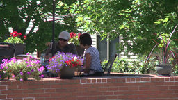 People eating at a sidewalk cafe with brick wall and potted flowers Footage