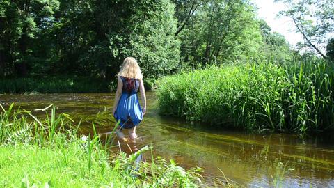 blonde girl long blue mottled dress wade through flowing river Footage