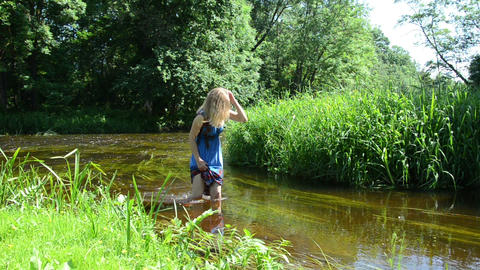 women wade in stream puts palm into the water pulls grass Footage