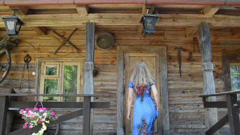 woman looking key over old house wooden door frame Footage