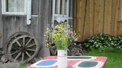 red table stand white vase small wild flowers on table rains Live Action