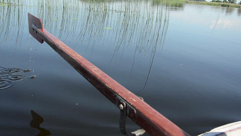 on dark lake water surface dripping small drops from paddle Footage